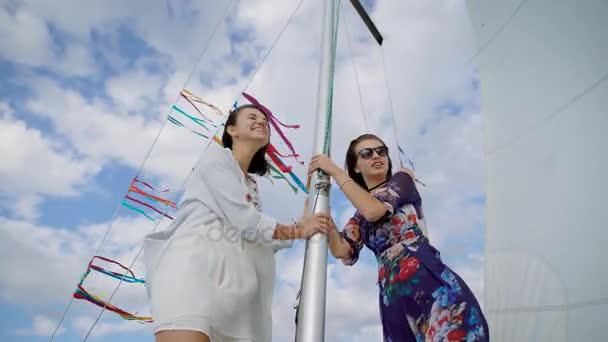 Two young stylish girls standing on modern sailboat posing happily