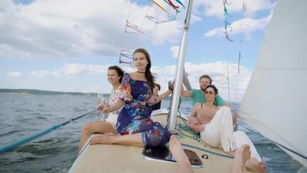 Cheerful group of young friends having party on modern yacht