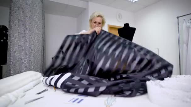Professionelle Couturier arbeitet in Nähwerkstatt holding schwarzes ...