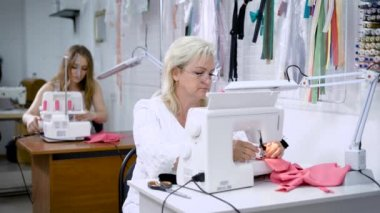 Two women sitting at the tables working on clothing manufacture. Woman sewing pink cloth on modern machine and cutting item with scissors. Girl in the background threading a needle for using overlock.