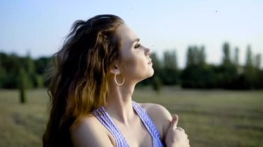 Beautiful young woman standing alone in the field, dreaming, wondering and smiling to warm summer sun