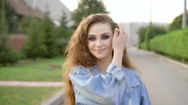 Amazing young woman walks on the street wearing jeans jacket, blue dress and smiling incredibly
