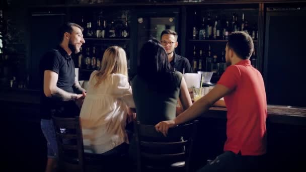 Back view of four young friends relaxing at bar counter talking with barman on the other side of wooden table. Company of people in casual clothes are having break together speaking with bartender.