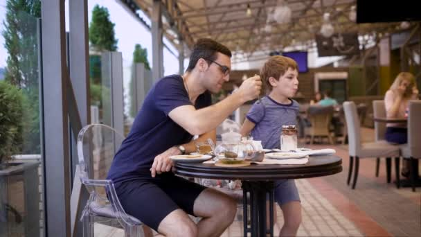 Handsome man in casual blue shirt and breeches sitting in restaurant with son and people in the background. Young father eating dessert of child with long teaspoon. Little boy talking to male parent.