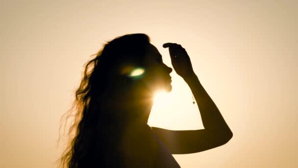 Oldalnézetből a névtelen nő pózol hátsó fény ég háttere.