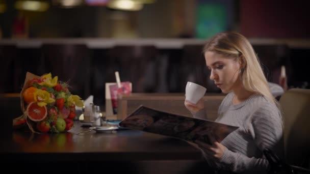 Žena s šálek kávy při výběru jídla z menu