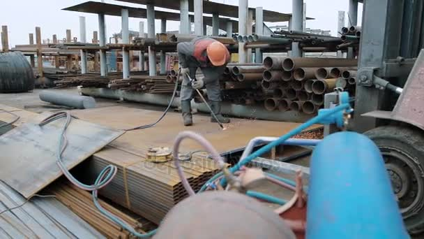 Industrial worker in fireproof uniform cutting metal sheet with propane gas  torch burner outdoor
