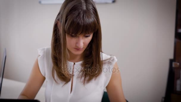 young brown-haired woman accountant is checking invoices and statements in an office during working day
