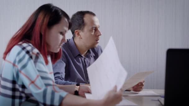 férfi és nő, egy ingatlanügynök társaság ügyfelek ül egy ügyfélszolgálati részleg és dokumentumok olvasása