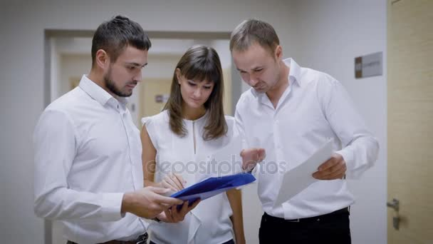 office workers are standing in a corridor of an agency building, holding folders with documents in hand, considering and debating