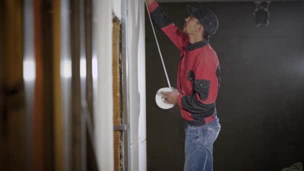 pracovník dělá značky na sádrokarton, připevňuje se na stěnu, lepení páskou, během opravy bytu