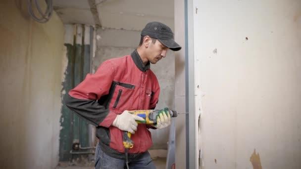dospělé opravář je vrtání děr do kovového profilu elektrickou vrtačkou uvnitř budovy na staveništi
