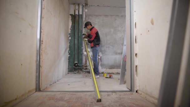 mistr je měření metr dlouhý hliníkový profil a dělání značek, stojící v opravě plochých