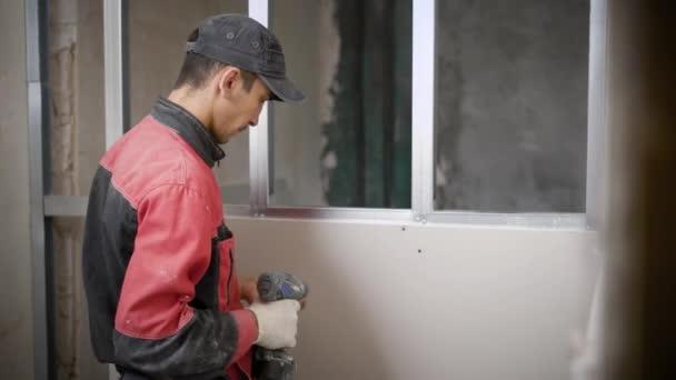 Opravář je upevnění sádrokartonových desek na profily, pomocí samořezných šroubů a elektrický šroubovák