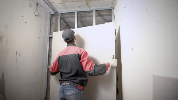 muž zvedl a úpravě sádrokartonových desek na hliníkové konstrukci, stavební práce uvnitř nového bytu