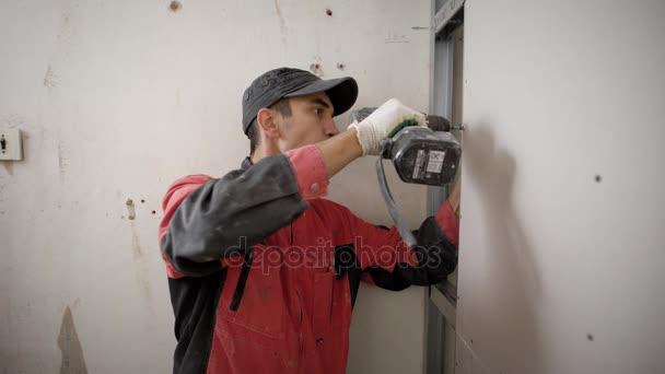 Instalační sádrokartonové konstrukce je utahoval šrouby do zdi, použití Akumulátorový šroubovák v pracovní den stavebního objektu