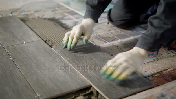 TILER je instalace keramická dlažba nad cementu a elektrické podlahové vytápění, zarovnání, pomocí budování úrovni, moderní technologie opravy