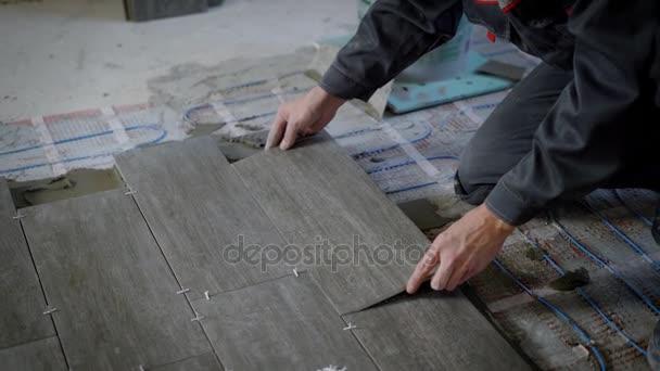 obkladač je lhaní dlaždice na podlaze, dolů a regulace, instalace plastových průmyslových kříže pro upevnění