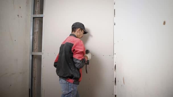 Stavební dělník je instalace nové sádrokartonové desky v bytě uniformě