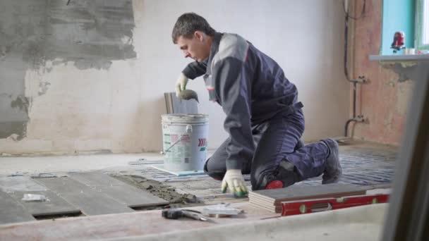 Profesionální pracovník je puttying betonovou podlahu v bytě