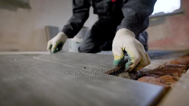 Blízký pohled na systémová stavební dělník se stanoví dlaždice lepené podlaze
