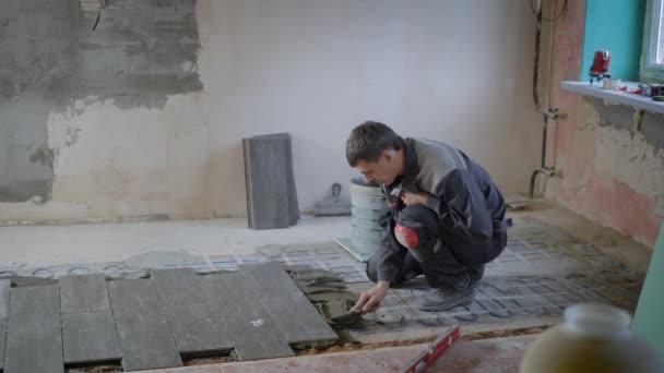 Stavební dělník položí dlaždice v bytovém domě pomocí speciálních nástrojů sám.
