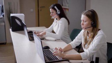 Several women print the text on the laptop keyboard, the ladies talk on the microphone in the call center office, they answer incoming calls and advise customers