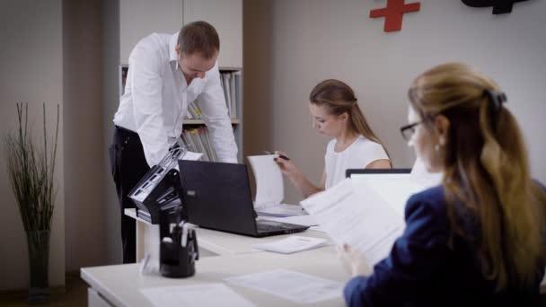 Plusieurs personnes regardent les documents dans le bureau lhomme
