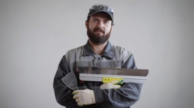 a portrait of an adult and a bearded man who is dressed in a construction uniform, people holding a spatula
