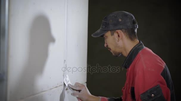 Un giovane che lavora come un generatore mette un bianco stucco