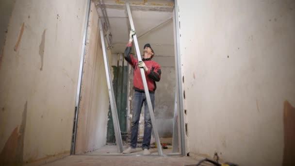 Tvůrce v rukavice nainstaluje falešnou stěnou, muž používá kovových profilů k vytvoření sádrové lepenky zeď