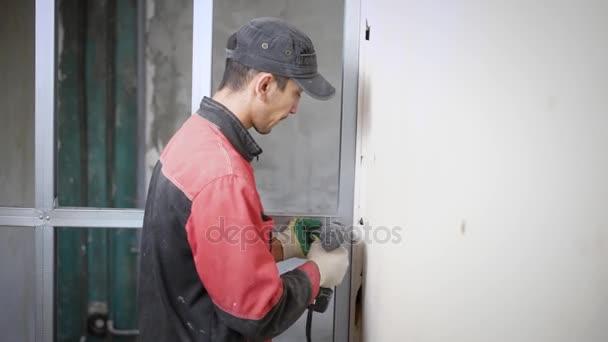 Portrét muže, který se umístil na montáž hliníkového profilu na zdi během rekonstrukce bytu