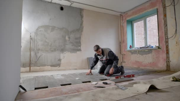 egy építője, aki dolgozik a lakás helyezi a csempe a padlón, és ellenőrzi a lejtőn és egyenletességét, a padló egy szinten