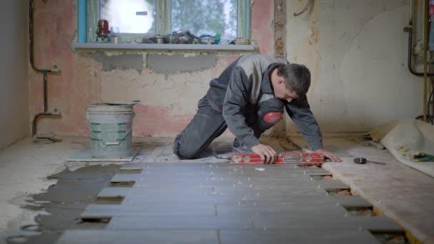 A munkavállaló épület formájában ellenőrzi a szint az a felület, a kerámia csempe, majd hozza a cement a padlóra, és egyesíti az új padló elem