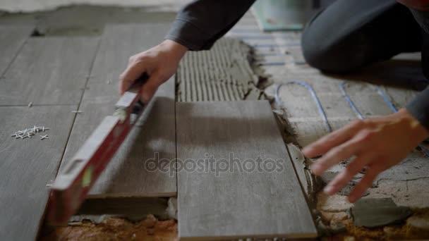 közelről lövés a kezében egy ember, aki ellenőrzi a kerámia csempe felszínének szintje alatt a csempézett padló fektetése