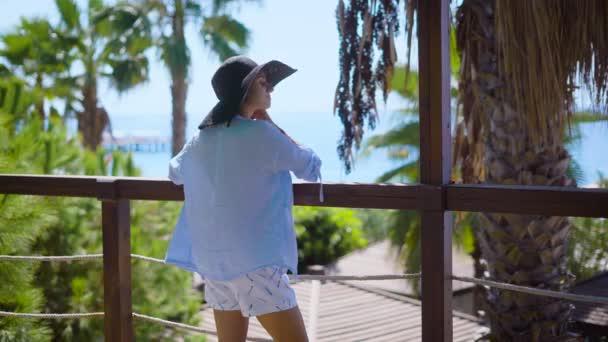 Woman standing on terrace of tropical hotel on ocean coastline
