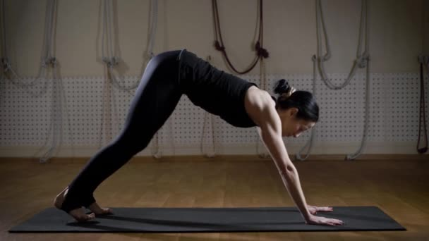 Sportovkyně dělá jógu na rohoži v útulné studio sám