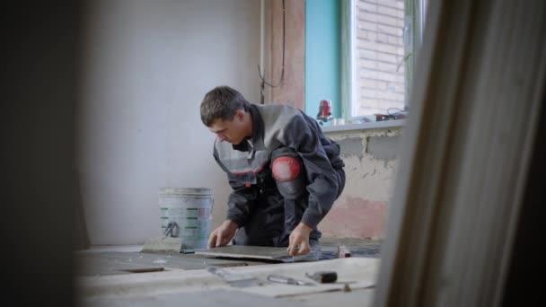 Koncentrovaná tvůrce zdobení podlahy v místnosti ve výstavbě s kameny