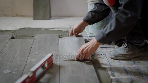 Uomo che lavora al cantiere posa di piastrelle su pavimento con