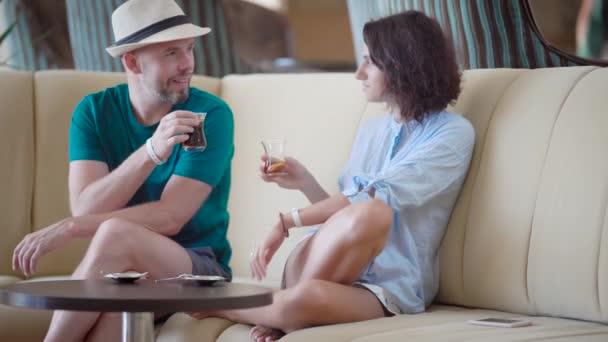 pár turistů sedí na pohodlný gauč béžové v luxusním hotelu v denní pití ledový čaj citron