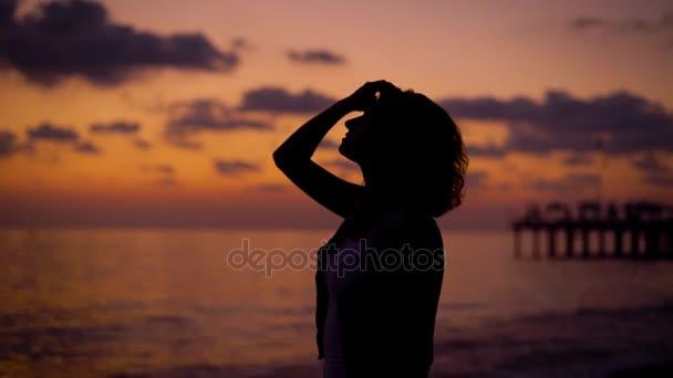 silueta ženy stojí na břehu moře v soumraku na pozadí slunce nebe, při pohledu na moře, skládání ruce v modlitbě a stoupající ruce