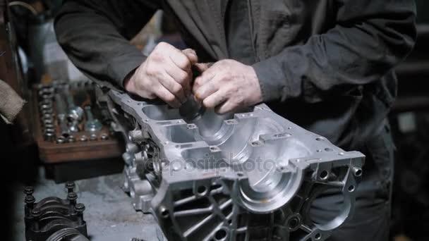 Nahaufnahme eines professionellen Mechanikers beim Demontieren des Motorblocks in einem Auto-Wartungszentrum.