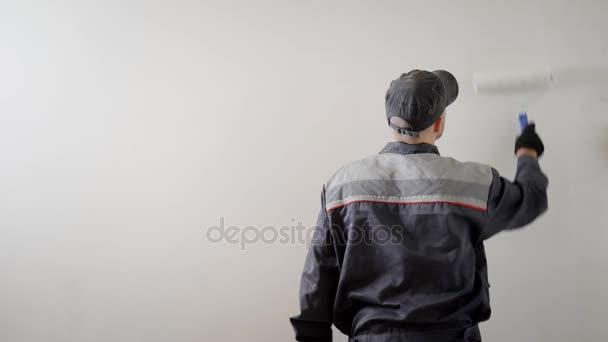 malíř je stojící zpátky a Vymalování stěn v bílé barvě, uvnitř místnosti, pomocí válečkem, pracovní den