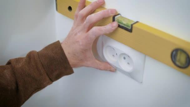 Wireman přibývá dvojitá zásuvka na bílé zdi uvnitř bytu, zarovnání a kroucení šrouby pomocí šroubováku