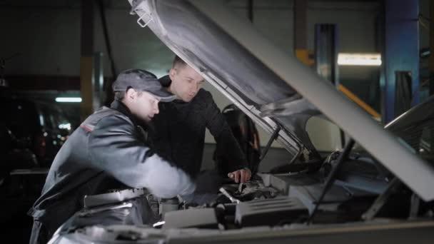Meccanico di automobile e cliente auto motore del controllo