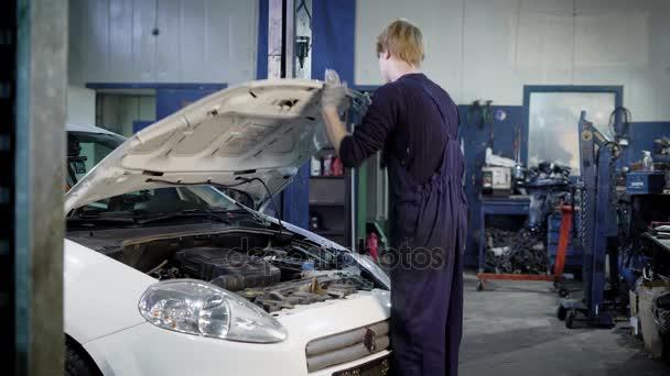automobilový technik je autoservis, otevření hood, osvětlení kapesní svítilnu a hledal poruchu
