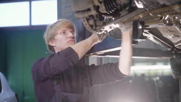 Mladý technik člověk dělat motor služebního auta v garáži.