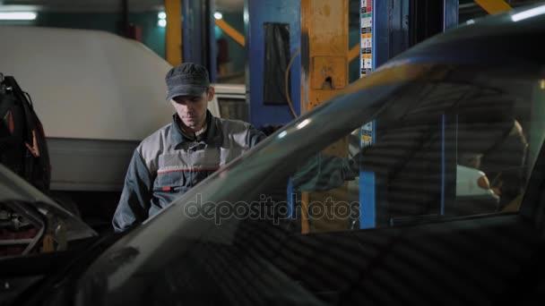 auto mechanik je zvedání auta, pomocí elektro Hydraulický zvedák v auto služby během naplánované kontroly automobilu