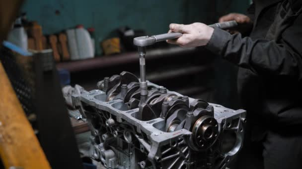 automotive technician is tightening bolts on a piston group in a car engine after repair in a auto-service