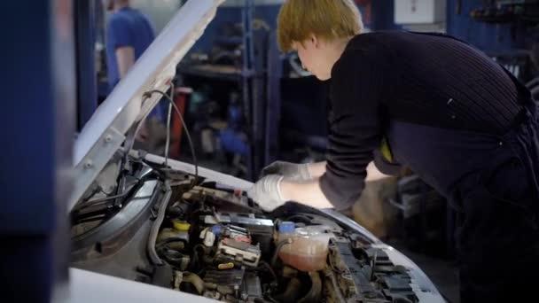 auto mechanik je demontáž energetické jednotky z vnitřní struktury vozu v temné workshop auto služby
